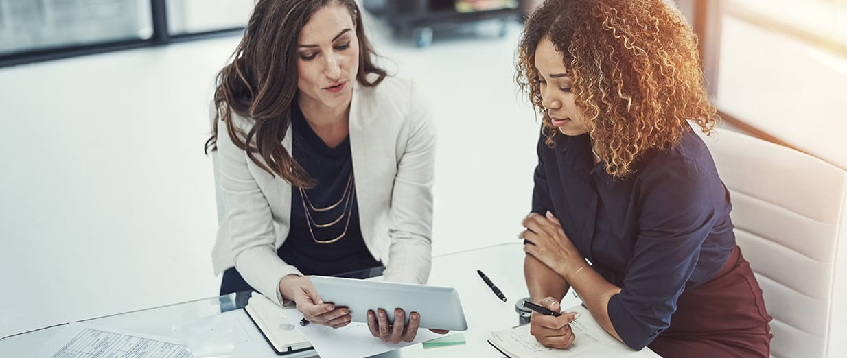 a white business woman showing a black business woman something on a tablet