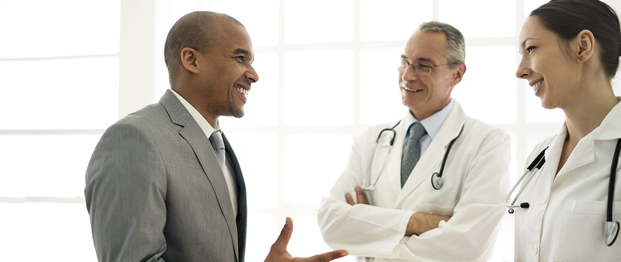man talking to a male and female physician